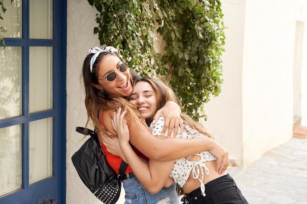 Twee zussen omhelzen elkaar op straat. voel je gelukkig en blij om samen te zijn.
