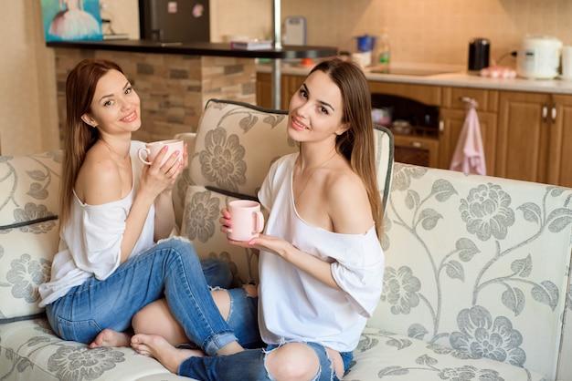 Twee zussen op de bank met een kopje thee in handen. twee beste vrienden die van tijd genieten.