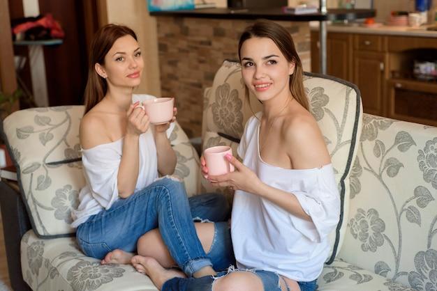 Twee zussen op de bank met een kopje thee in handen