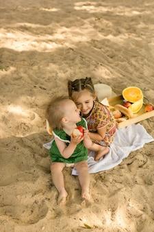 Twee zussen op een zandstrand in de buurt van de zee lachen vrolijk en eten fruit en snoep die hun ouders hebben verzameld voor een picknick