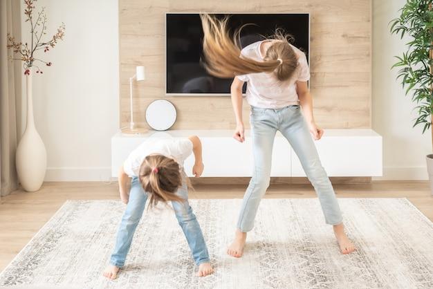 Twee zussen plezier dansen in de woonkamer