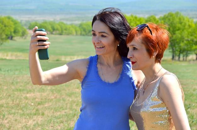 Twee zussen praten met vrienden tijdens een videogesprek via de mobiele telefoon