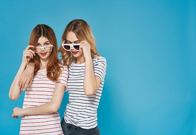 Twee zussen staan naast elkaar modieuze kleding studio luxe vriendschap blauwe achtergrond