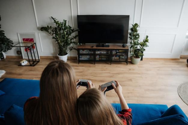 Twee zussen thuis hebben plezier en spelen een console met een joystick