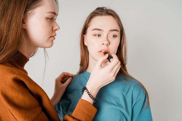 Twee zussen tweeling mooie meisjes in casual schilderij lippen doen