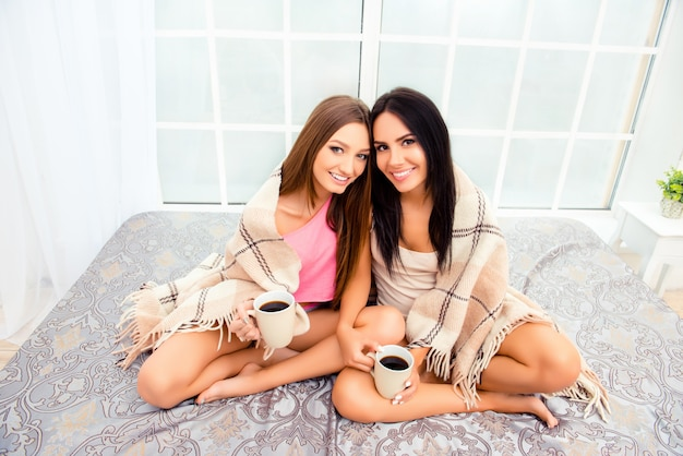 Twee zussen zitten op bed en zonnebaden met plaid en thee