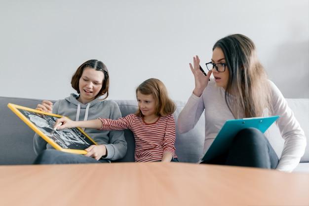 Twee zustermeisjes praten met jonge vrouw familie psycholoog