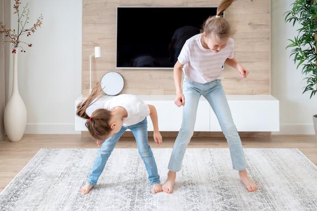 Twee zusters die pret hebben die in woonkamer dansen, gelukkig familieconcept