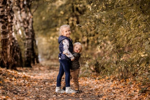 Twee zusters kleine meisjes lopen in het herfstbos