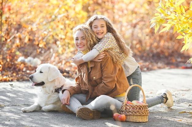 Twee zusters op herfstachtergrond. meisjes hebben buiten plezier met hun huisdier. mensen en hond.