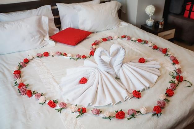 Twee zwanen gemaakt van handdoeken die hartvorm op bed vormen
