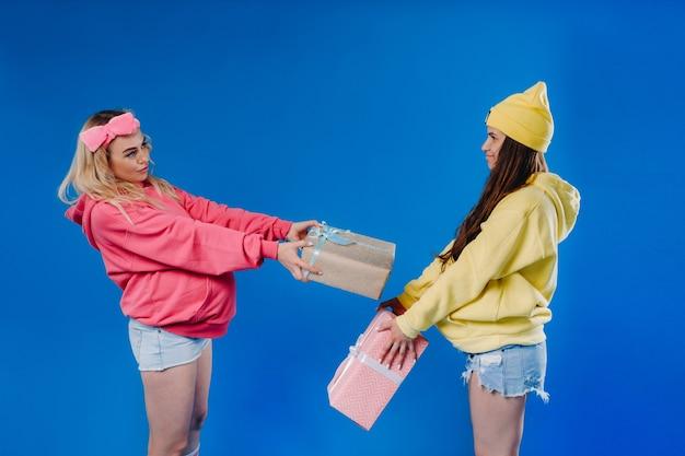 Twee zwangere meisjes met geschenken in hun handen op een blauwe geïsoleerde achtergrond.
