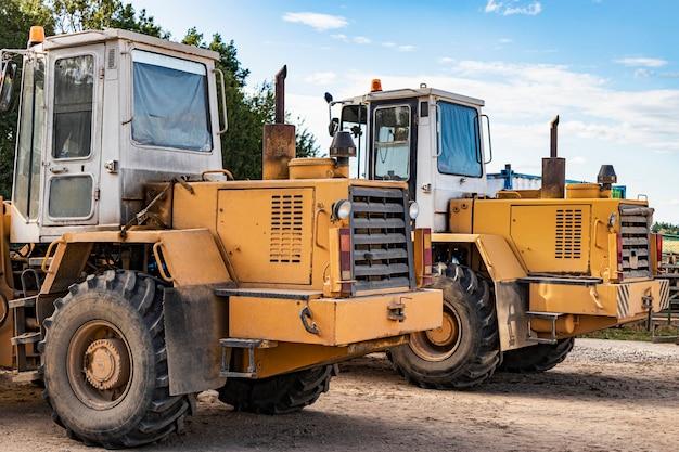 Twee zware wielladers staan op een bouwplaats. apparatuur voor grondwerken, transport en laden van bulkmaterialen - aarde, zand, steenslag.