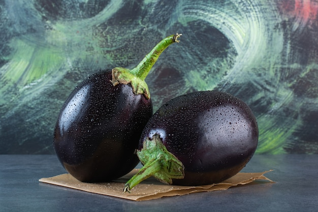 Twee zwarte aubergines met waterdruppel op stenen achtergrond.