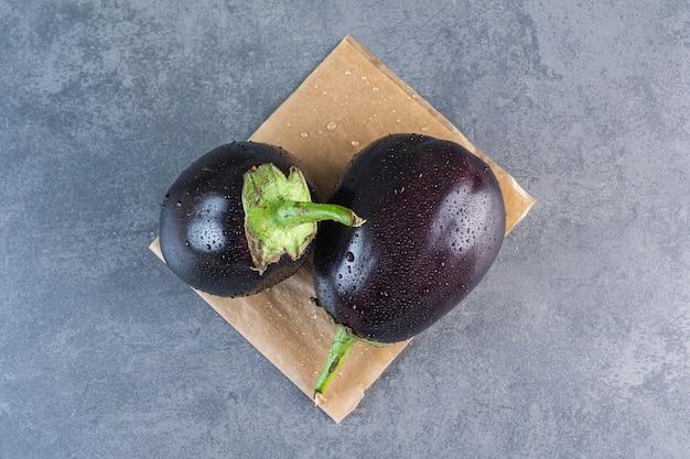Twee zwarte aubergines met waterdruppel op stenen oppervlak