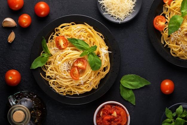 Twee zwarte borden met vegetarische smakelijke klassieke italiaanse spaghetti pasta met basilicum, tomatensaus, parmezaan en olijfolie op een donkere tafel. bovenaanzicht, horizontaal.