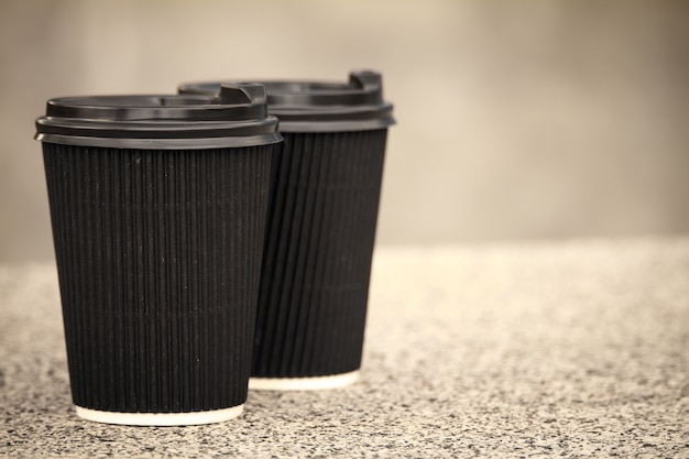 Twee zwarte eenmalige kopjes koffie met deksels staan op de stenen borstwering