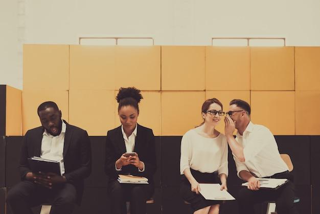 Twee zwarte en twee witte managers die op stoelen zitten