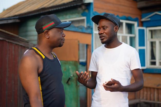 Twee zwarte kerels bespreken bedrijfskwesties op achtergrond van een dorpshuis