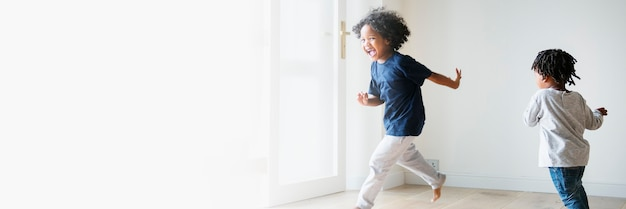 Twee zwarte kinderen die elkaar spelen en achtervolgen in een lege ruimte met tekst