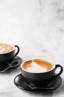 Twee zwarte kopjes hete latte koffie met mooie melk schuim latte kunst textuur geïsoleerd op heldere marmeren achtergrond. bovenaanzicht, kopieer ruimte. reclame voor café-menu. coffeeshop menu. verticaal