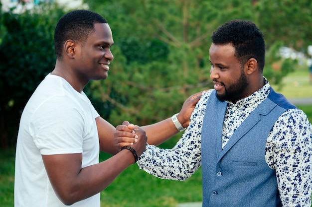 Twee zwarte mannen in stijlvolle pakken ontmoeten elkaar in een zomerpark. afro-amerikanen vrienden spaanse zakenman begroeten elkaar teamwerk buitenshuis