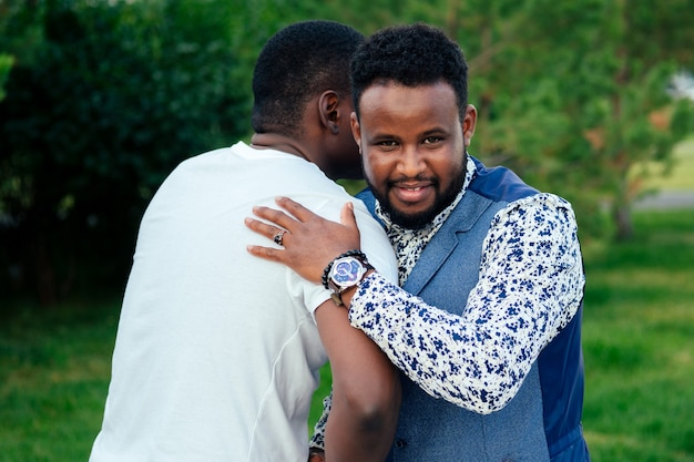 Twee zwarte mannen in stijlvolle pakken ontmoeten elkaar in een zomerpark. afro-amerikanen vrienden spaanse zakenman omarmen knuffel begroeten elkaar teamwerk buitenshuis.