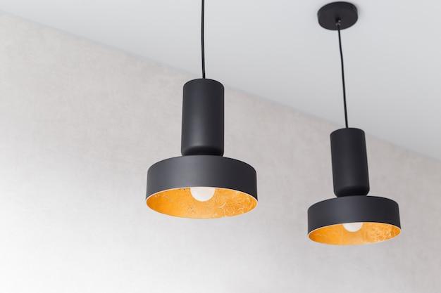 Twee zwarte metalen hanglampen aan de binnenkant versierd met gouden folie