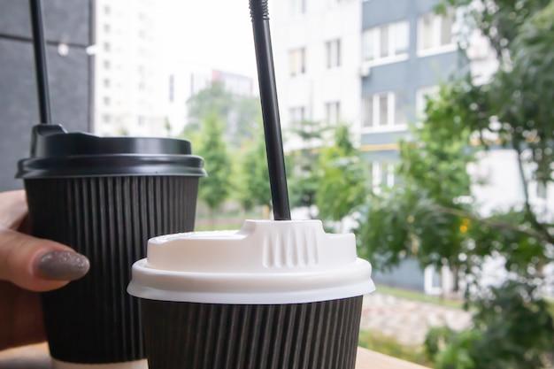 Twee zwarte papieren koffiekopjes met deksels buiten in de zomer bij zonnig weer op een houten tafel van een café, koffieshop of restaurant.