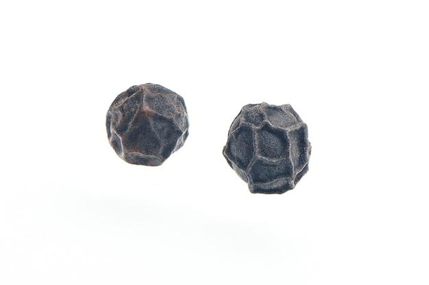 Twee zwarte peperkorrels die op witte hebben worden geïsoleerd. hoop van droge peperkorrels. zwarte peper zaden close-up bekijken.