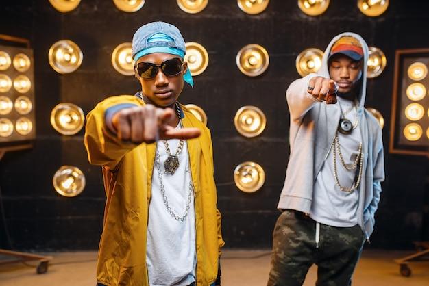 Twee zwarte rappers in petten, artiesten poseren op het podium