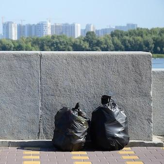Twee zwarte vuilniszakken op betegelde straatvloer bij concrete omheining in stad