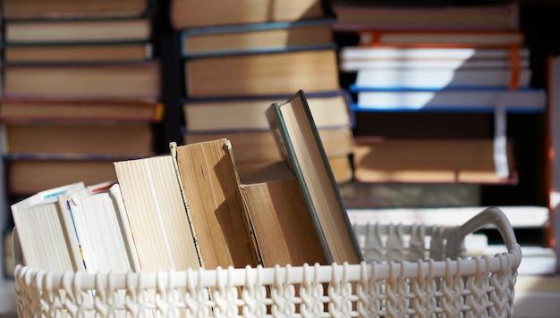 Tweedehands boeken op een witte mand met boeken op de achtergrond