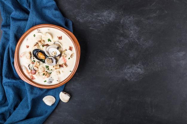 Tweekleppig schelpdierensoep in een bruine plaat. de hoofdingrediënten zijn schaaldieren, bouillon, boter, aardappelen en uien.