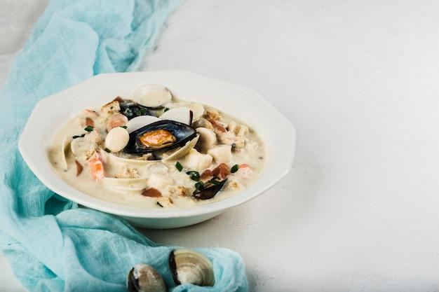 Tweekleppig schelpdierensoep in een witte plaat. de hoofdingrediënten zijn schaaldieren, bouillon, boter, aardappelen en uien.
