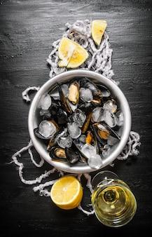 Tweekleppige schelpdieren in een beker met ijs, wijn en citroen. op een zwarte houten tafel. bovenaanzicht