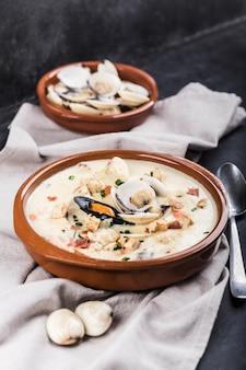 Tweekleppige schelpdiervissoep in een bruine plaat. de hoofdingrediënten zijn schelpdieren, bouillon, boter, aardappelen en uien.
