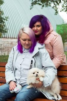 Tweekleurig haar lesbisch hand in hand en glimlachend gelukkig homoseksueel paar buiten