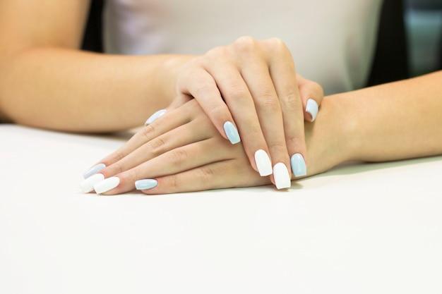 Tweekleurige manicure met blauwe en witte nagellak op een wit