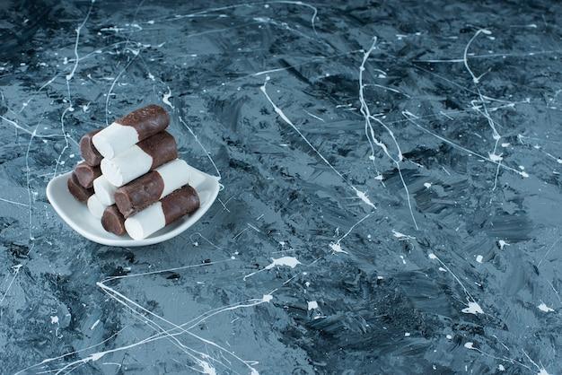 Tweekleurige snoepjes op een bord, op de blauwe tafel.