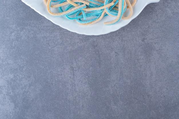 Tweekleurige touwvormige snoepjes op een bord op marmeren tafel.