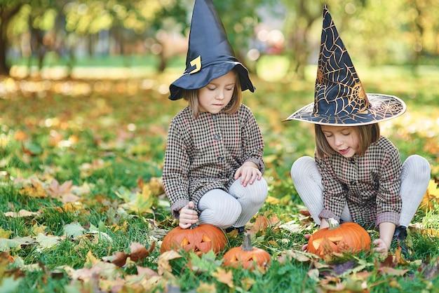 Tweeling in heksenkostuum tijdens halloween