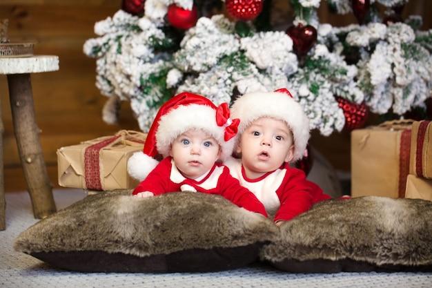 Tweeling in nieuwjaarskostuums, liggend op het bed, glimlachend en verheugd