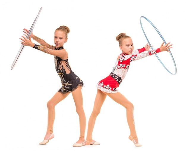 Tweeling meisjes doen gymnastiek oefeningen met hoepels.