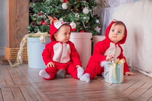 Tweeling-peuters in rode santa's rendierpakken zitten naast elkaar thuis tegen de achtergrond van de kerstboom