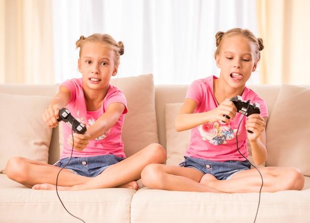 Tweeling speelt videogame met joysticks in handen.