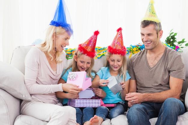 Tweeling uitpakken verjaardagscadeau met hun ouders