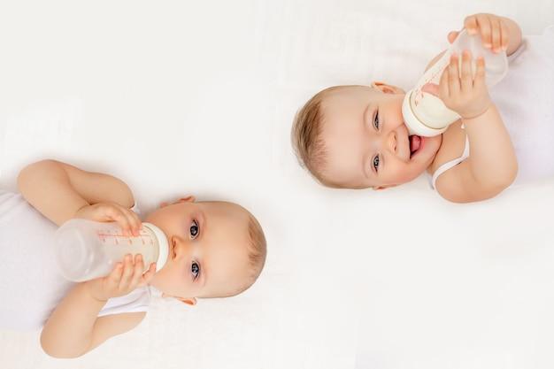 Tweelingbabysjongen en meisje met een fles melk op een wit bed thuis, babyvoedingsconcept