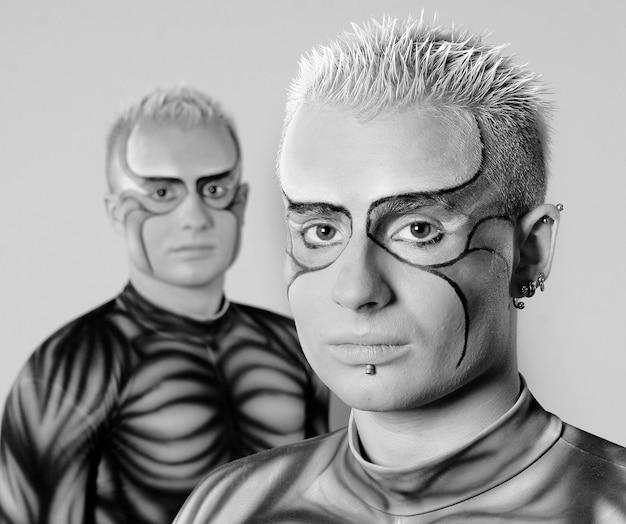 Tweelingbroers met artistieke make-up op gezicht in strakke pakken. gespierd lichaam