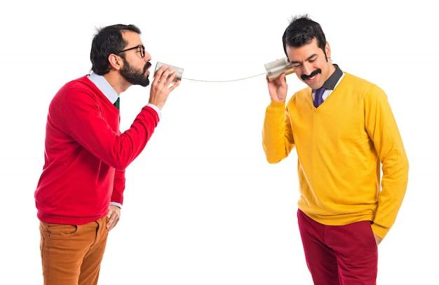 Tweelingbroers praten door een tin telefoon